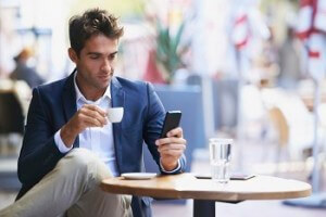 Shot of a young businessman reading a text while sitting at an outdoor cafe