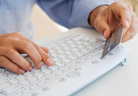 man paying with credit card on computer