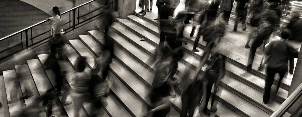 Many people walking fast on staircase
