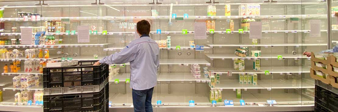 Man standing in front of empty shelves in supermarket trying to restock product