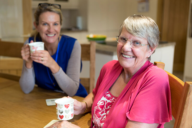A nurse and an old lady have tea and smiling