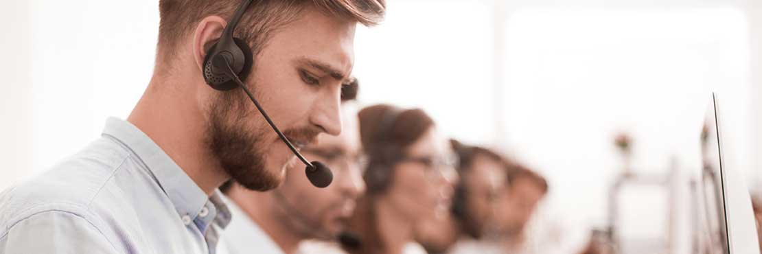 A man wearing a headset working in a call center