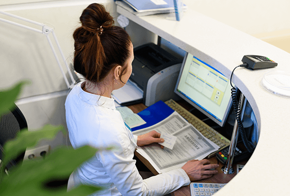 Nurse at reception working on a computer