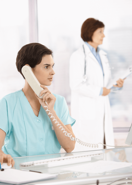 Nurse using the phone while working on a computer