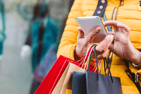 Women holding shopping bags and using her mobile phone