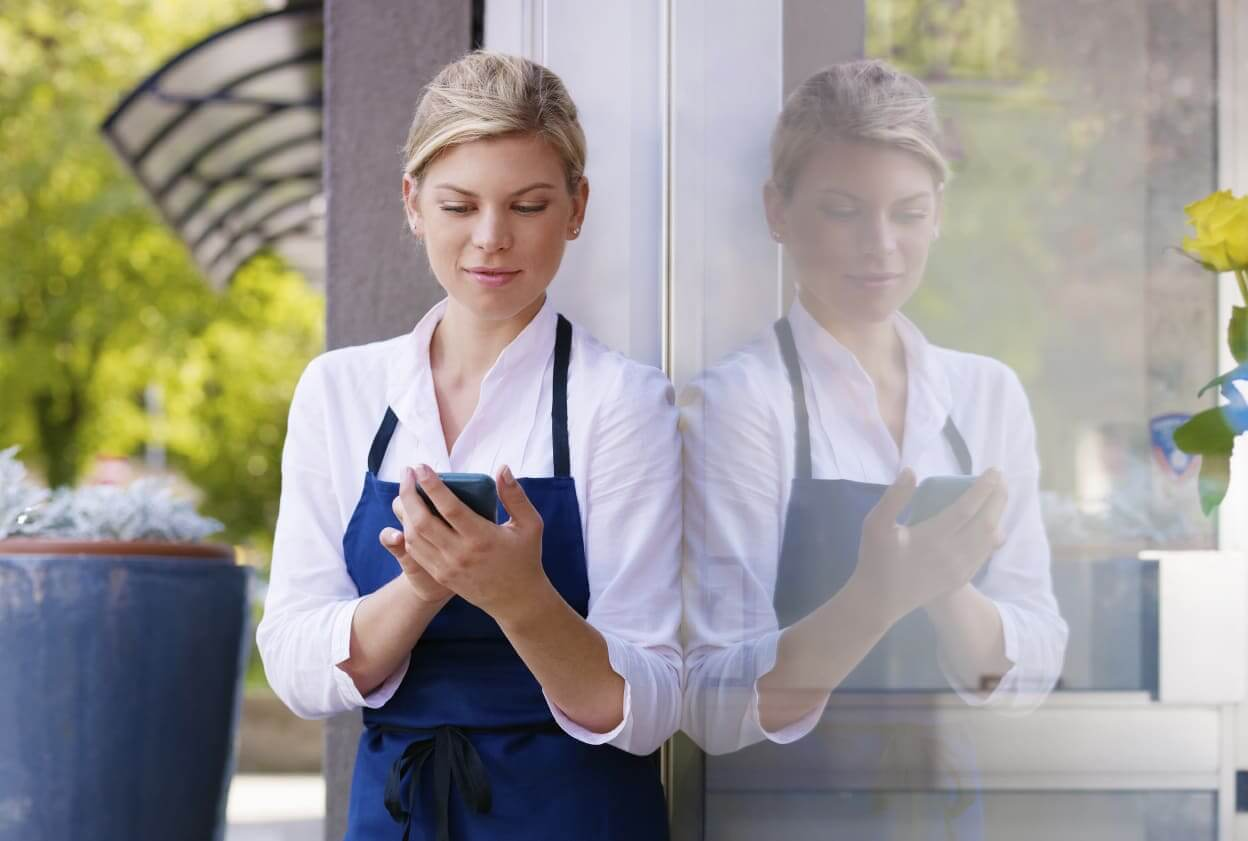 Waitress looking at mobile phones on break
