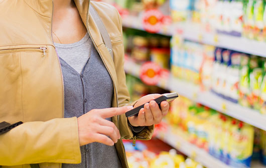 Woman shopping supermarket with phone in hand