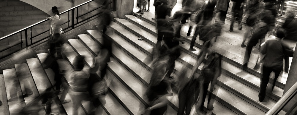 Black and white photo of lots of people walking across staircase