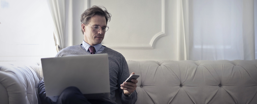 Man sat in business entire, looking at mobile phone while working on laptop