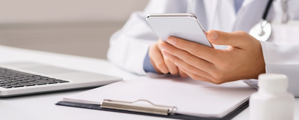 Doctor sat with mobile phone, clipboard, laptop and pill bottle