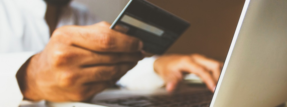 Person shopping online with bank card in hand