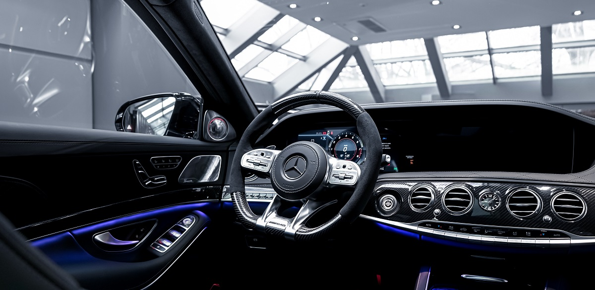 Inside of a new car. Focus on steering wheel and dashboard