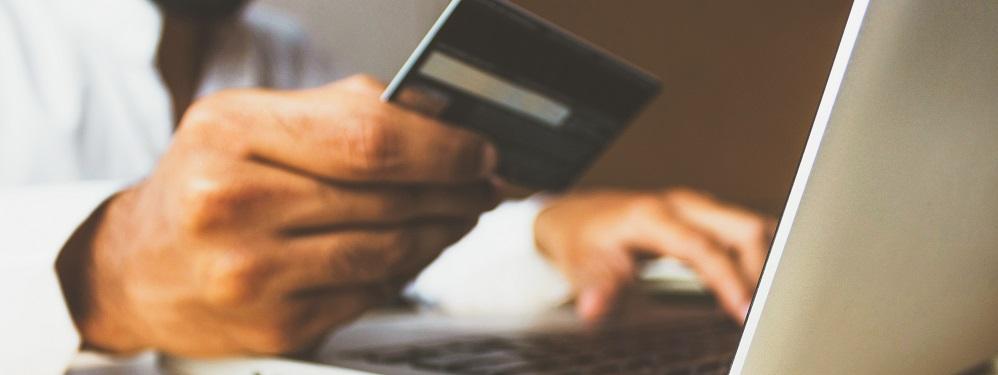 Laptop und Hand mit Kreditkarte