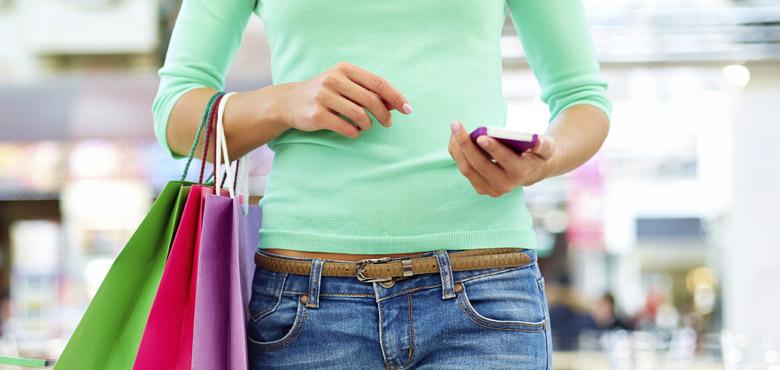 frau mit einkaufstüten und smartphone