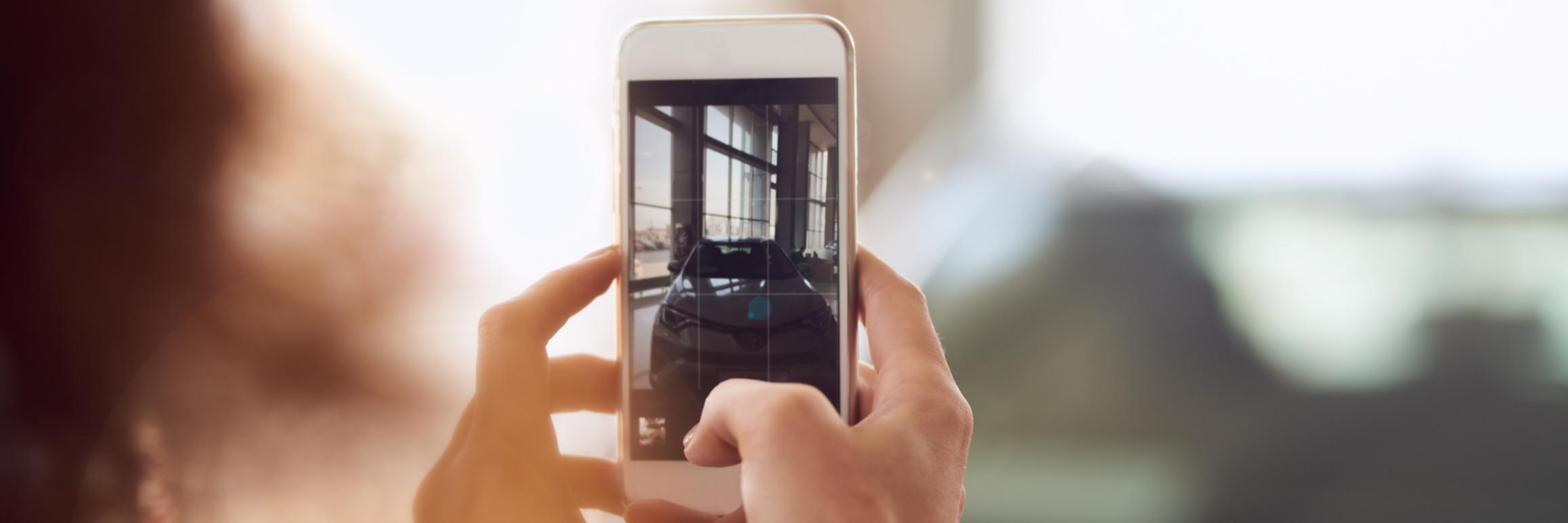 A women taking photo of a car
