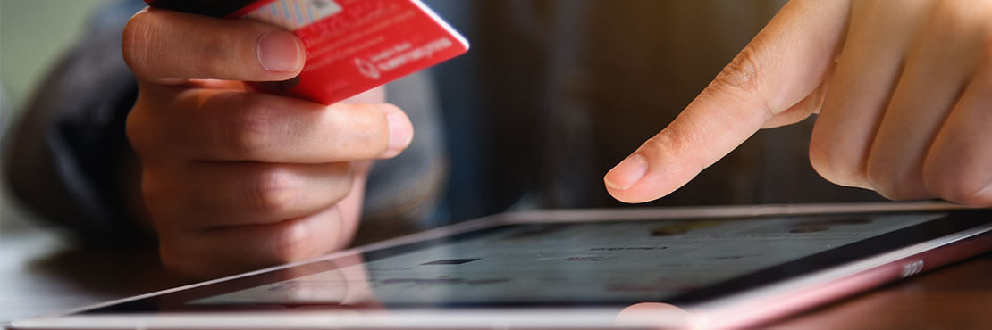 A man holding a credit card on one hand and scrolling on an tablet