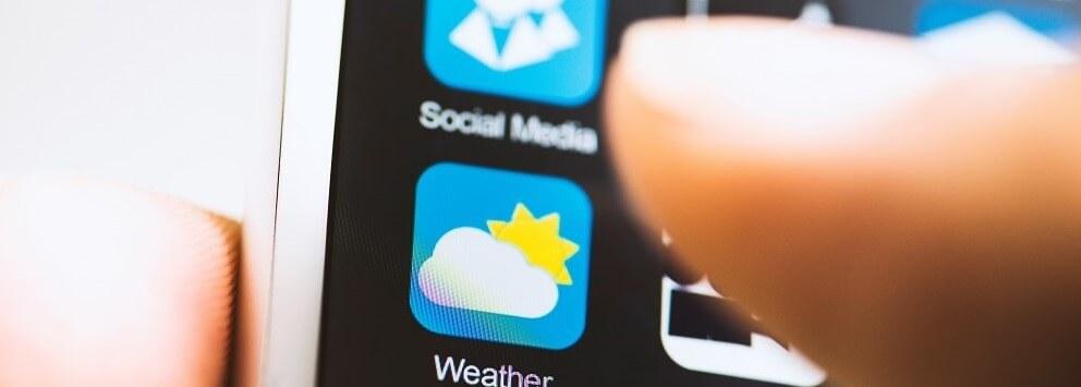 Hand die auf Wetter-App tippt