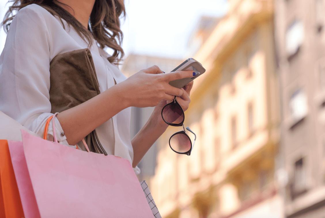 Frau beim Einkaufen mit Smartphone in der Hand