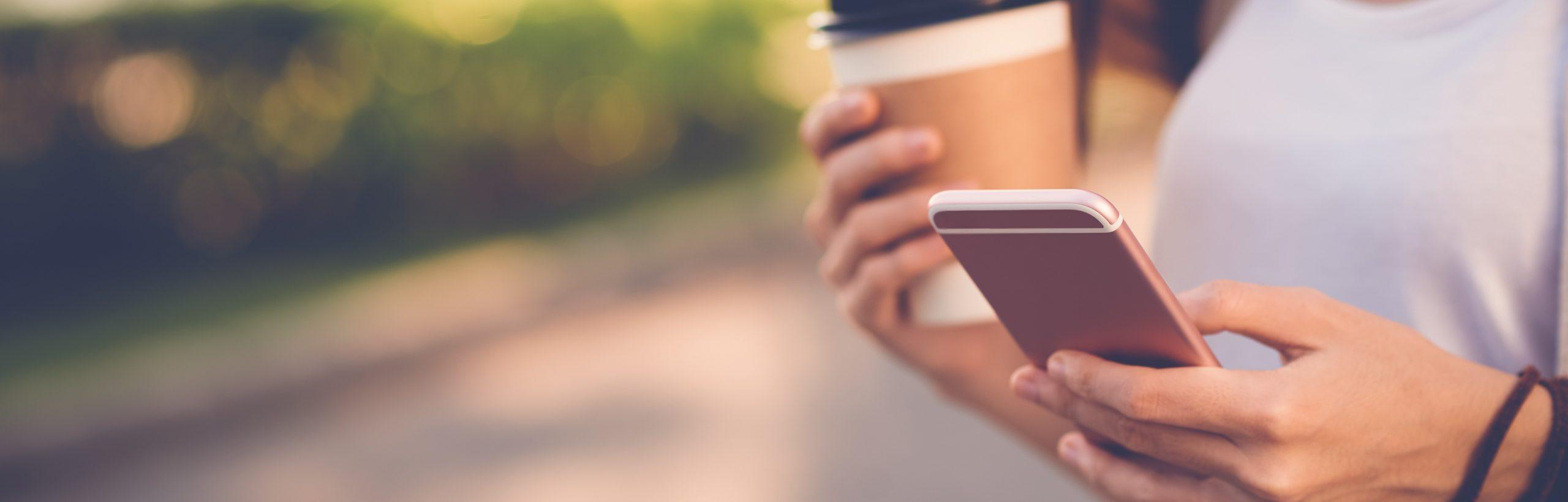 Frau mit Smartphone und Coffee-to-Go