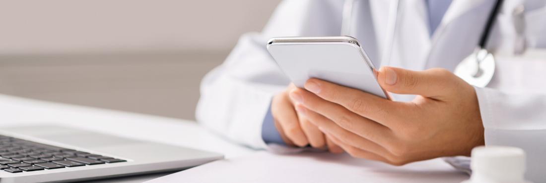 Doctor vestido con bata blanca sujetando un móvil en la mano