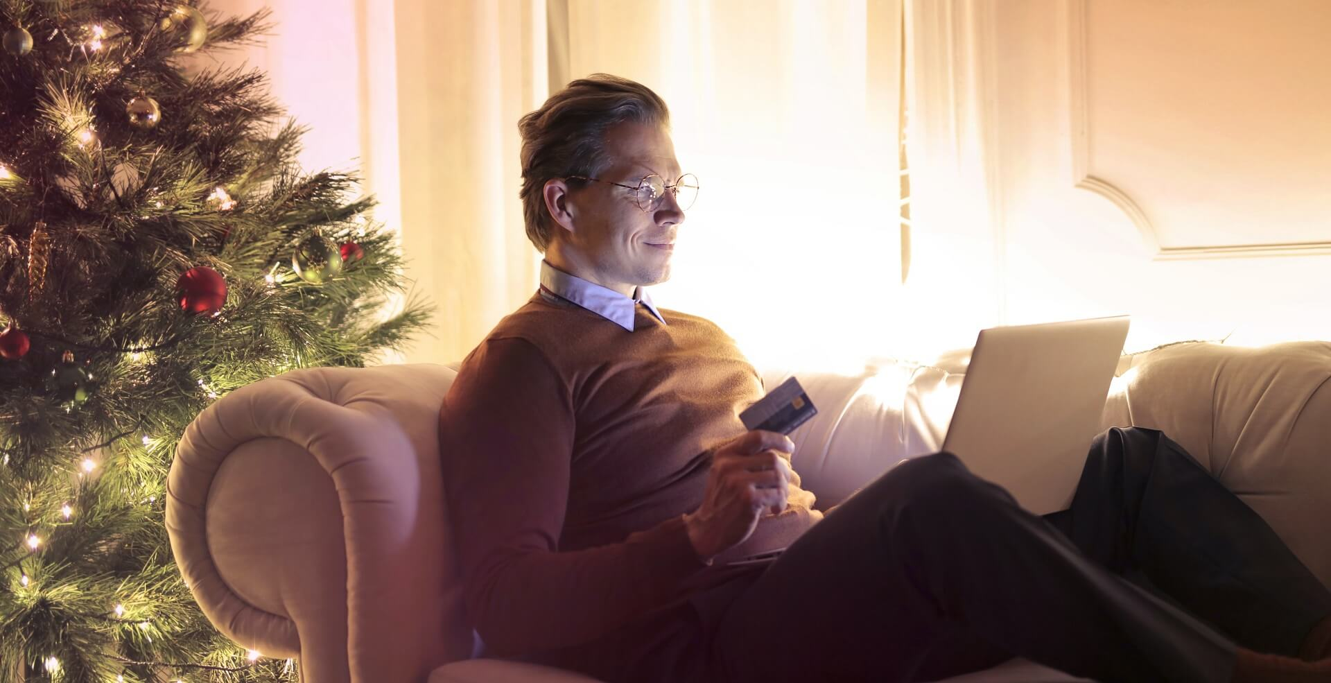 Man on sofa with credit card in hand presumably internet shopping