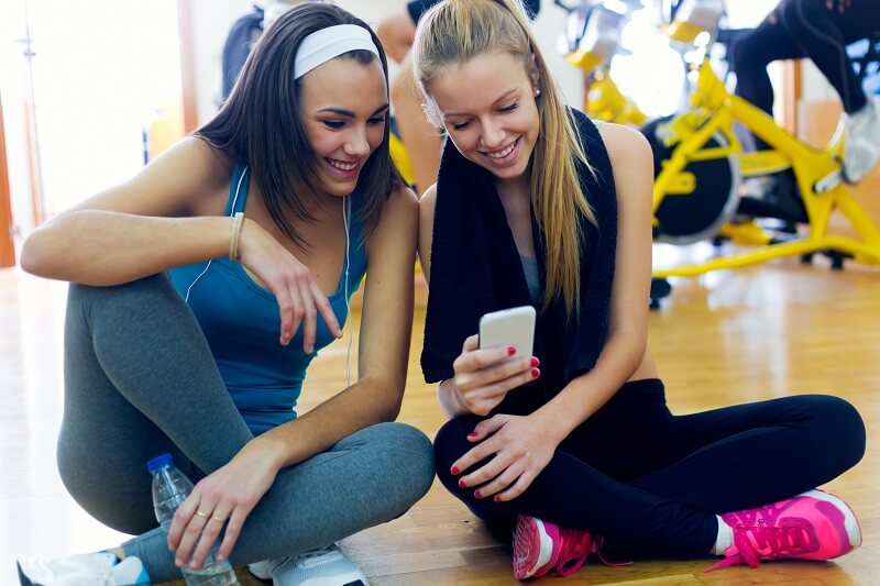 Portrait of young women using mobile phone in the gym.