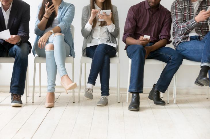 Gente sentada leyendo SMS en su móvil