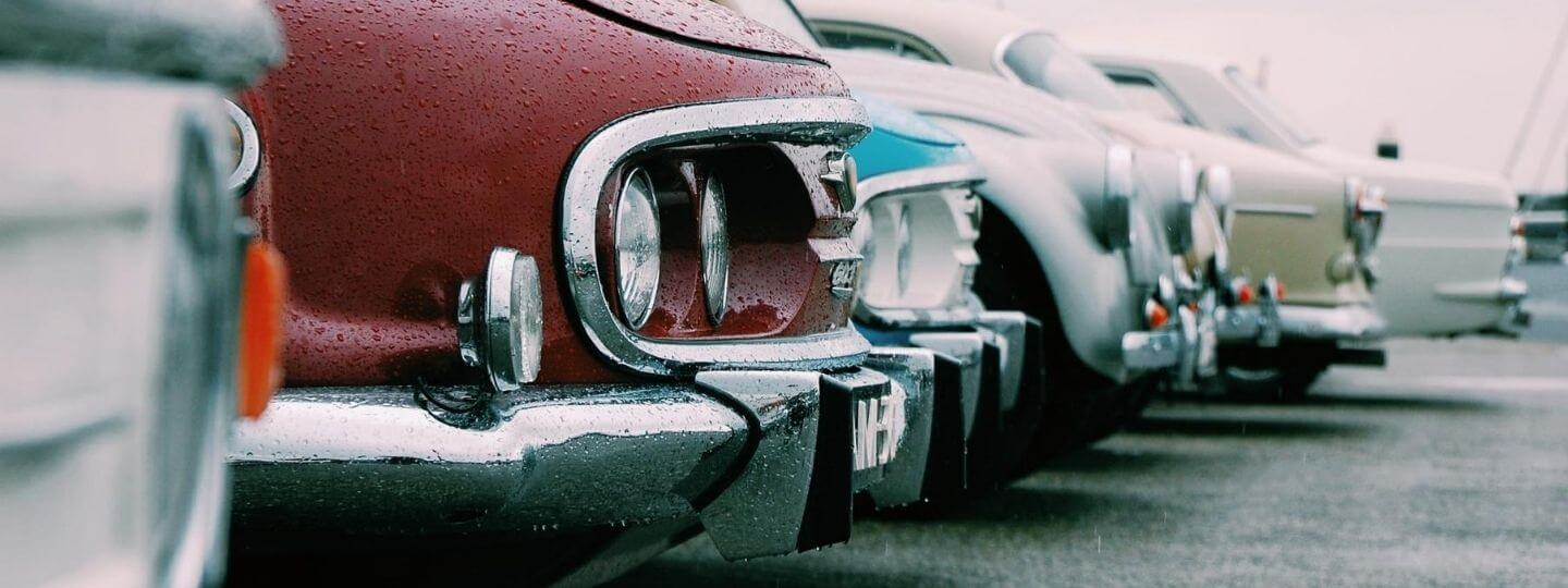 Featured image of vintage cars lined up at an outside show room