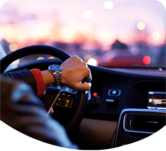 Photo of person with hand on steering wheel, driving a car