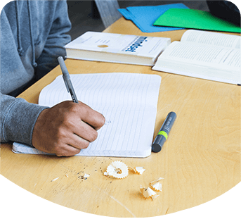 Photo of child sat at school desk with notebook, book and pens and pencils