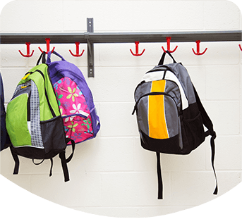 Childrens back packs hanging from hooks in school environment